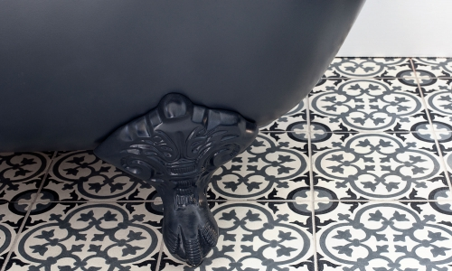 Image: Dark grey-floored wetroom with encaustic flooring and freestanding bath