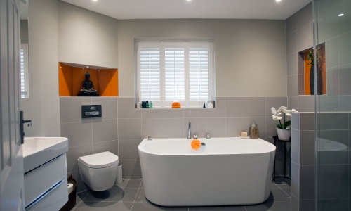 Image: Modern, minimal main bathroom with orange accents