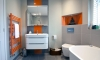 Modern, minimal family bathroom with orange accents —
