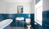 Blue-tiled main bathroom with slipper bath and geometric flooring —Hove