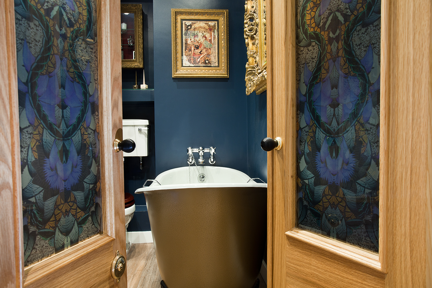 Image: Glamorous bathroom boudoir with rich blue walls and gold accents