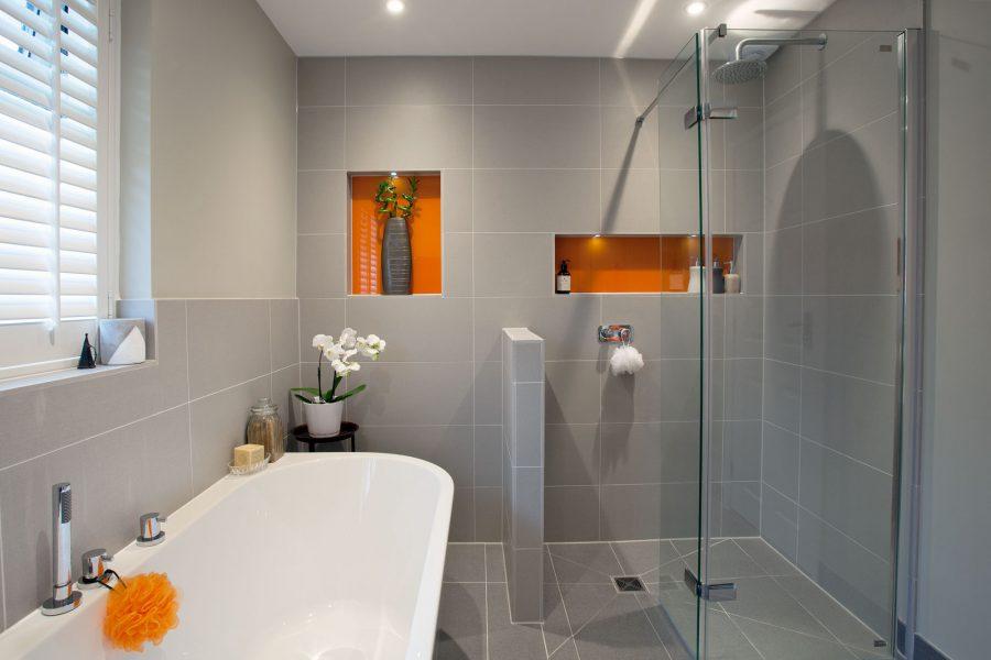 Modern, minimal main bathroom with orange accents ...